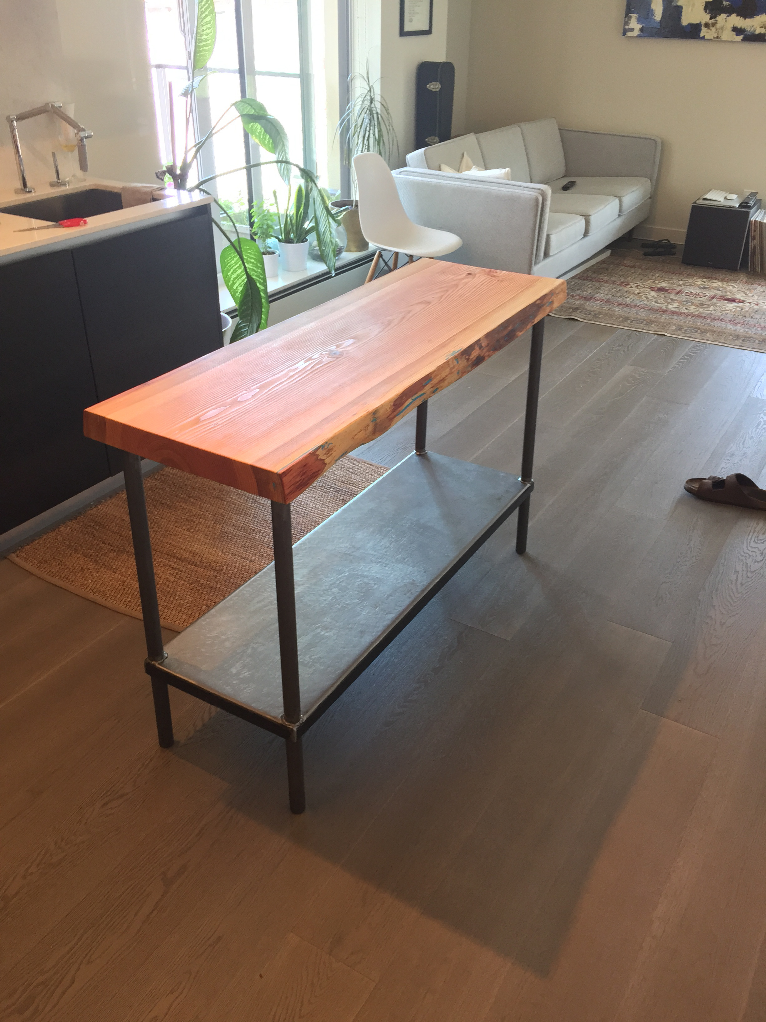 A Kitchen Island Made From Hornby Island Fir Supported By A Rustic Metal  Base.